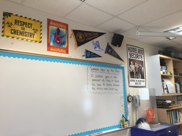 "Part of my white-board (cute, colorful border again) and wall decor. We are an AVID school, so I am sporting an AVID pennant as well as some colleges too. Of course I have some fun ""Sciencey""/nerdy posters on my wall (I have to show my personality!)."